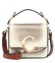 Chloé's compact Chloé C Mini shoulder bag has been crafted in Italy from glossy patent calf leather in a rustic ivory and beige palette. The label's signature C hardware adds cool recognition, and a reptile-effect panel brings . Cheap Handbags Online, Latest Handbags, Chloe Handbags, Gucci Handbags, Fashion Handbags, Purses And Handbags, Fashion Bags, Gucci Purses, Luxury Handbags