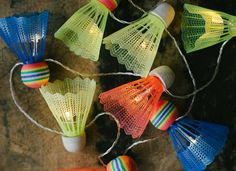 Turn a set of badminton shuttlecocks and old string lights into a cool decorative lighting idea for your next backyard party
