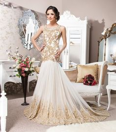 Elegant sleeveless gown, heavily crystallised to the hip point with swarovskis, diamontes and bead work. Beautifully finished with a gold lace border and trail.