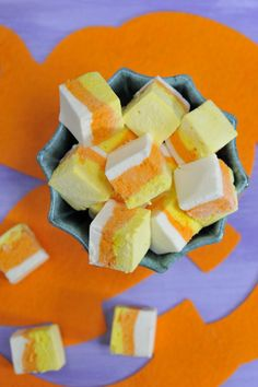 DIY Candycorn Marshmallows. instead of marshmallows use cake batter and food coloring. frost with white frosting and slice them in squares. creating candycorn cakes.
