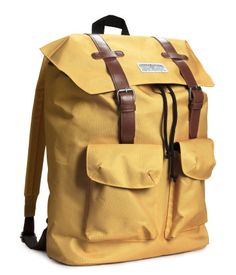 Yellow backpack in woven fabric with imitation leather details. Drawstring and flap at top, handle & adjustable shoulder straps. Two outer pockets with Velcro fasteners. | H&M For Men