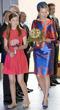 Matilde de Bélgica escogió un vestido de manga francesa en naranja con estampado 'azul klein', que combinó con un sombrero y salones al tono. Completó su estilismo con unos guantes en naranja.
