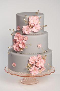 Pasteles de fondant para boda - los capullos rosa y los detalles dorados se destacan contra el fondo de fondant liso en gris de este pastel