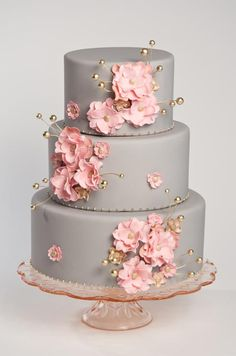 Pink blossoms and gold details pop against a sleek gray fondant- covered cake.