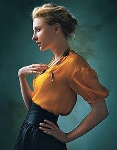 Cate Blanchett. The colours are beautiful.    This photo seems to have come from a magazine shoot.    Mustard yellow princess seamed, puff-sleeved blouse in a floaty fabric, possibly silk or chiffon. High waisted black skirt which seems to be made of something vaguely reflective- my first guess was leather, but now I'm more inclined towards a woven fabric with some sort of treatment.