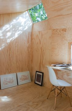 nestled in the backyard of a creative couples' brooklyn, new york home, is the 'writing pavilion'. an isolated place to escape, the small studio was designed by architects alessandro orsini and nick roseboro of architensions. the dwelling is clad with black stained cedar, which strongly departs from the interior's natural pine plywood.