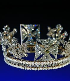 The 1820 Diamond Diadem made for George IV by Rundell, Bridge & Rundell, openwork silver frame lined w/gold, set transparent with 1,333 diamonds including a 4-carat pale yellow brilliant in center front cross. It has been worn regularly by queens regnant and consort from Queen Adelaide onwards since George IV's use in 1821. Her Majesty now wears it when traveling to and from the State Opening of Parliament.