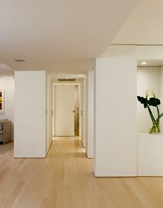 Ocean Boulevard Apartment, MADE Architecture. Entry hall with clean white walls, light wood floor.