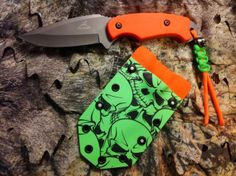 "Gerber ""Zombie Assault Knife""  Gerber knife (I don't remember model). Signal Orange G10 scales, Signal Orange & - Green Paracord, Metal skull with glow in dark eyes.  Sheath: Tactical Infusions Zombie Green Skull Kydex (Awesome stuff!) & Signal Orange Kydex, belt loops with rubber silencers, glow in dark dots."