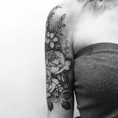 Tatuagem criada por Gabriela Blaezer do Rio de Janeiro. Braço com diversas flores em blackwork.