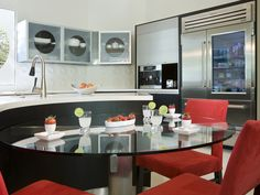 The black and white color palette of this kitchen is accented with bright red chairs, giving the space a '50s feel. The textured backsplash and unique glass cabinet doors add more visual interest in the room, designed by Elizabeth Rosensteel. http://www.hgtvremodels.com/kitchens/kitchens-that-pop-with-color/pictures/index.html?soc=KB14