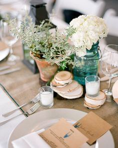 The florist finished the table decor with jars of hydrangeas and terracotta pots of rosemary.