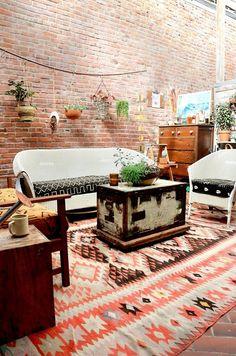 Sala com decoração boho com tijolos aparentes , plantas , estampas étnicas ,...
