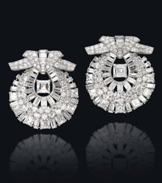 A PAIR OF ELEGANT ART DECO DIAMOND CLIP BROOCHES, BY CARTIER  Each of shield-shape set with lines of brilliant, square and baguette-cut diamonds, centering upon a larger square-cut diamond, to the pavé-set stylized bow surmount with baguette-cut diamond line detail, 1938, 5.0 cm each, with French assay marks for platinum, in red leather Cartier case Both with maker's mark and signed Cartier, no. 607