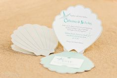 Sea Shell Shaped Cut Out Wedding Invitations And Various Day Of Items Such As Table Names Numbers Menus Programs To Name A Few