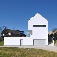 Slovenian studio Arhitektura d.o.o. have completed a gabled house with a crisp white silhouette just outside the medieval town of Škofja Loka