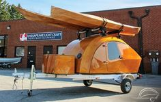 This is a gorgeous teardrop trailer by Chesapeake Light Craft. From the outside, you'll notice a highly polished wooden tiny camper with a sturdy roof rack that can carry two kayaks. Accordin…