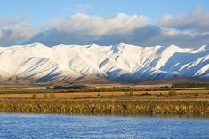size: Photographic Print: The Ben Ohau Range cloaked in autumn snow, the Pukaki Canal in foreground, Twizel, Mackenzie distri by Ruth Tomlinson : New Zealand Landscape, South Island, Mountain Range, Cloak, Cold Temperature, Poster Size Prints, White Image, Natural Beauty, Photo Wall Art