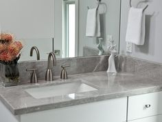 a sleek and clean look is created in this modern bathroom with gray marble countertops and