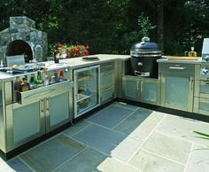 This large L-shaped outdoor kitchen design includes paneled cabinetry by Danver, a bar center, refrigerator and smoker.   Contact us for assistance… …