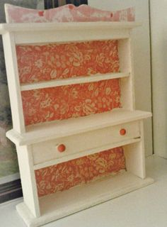 Miniature Hutch for a little girl's room in a dollhouse. Painted ivory then decoupage with coordinating scrapbook papers. Drawer pulls are touched with a coral-pink to match the paper background.