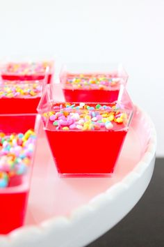 New Years' Eve Champagne Jello Shots  1 package of raspberry (or your favorite flavor) jello, 1 cup boiling water, 1 cup Delamotte Champagne or Bulletin Place Sparkling Moscato, Sprinkles