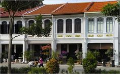 """Singapore shophouse facades are known for their mix European Neo-Classical and traditional Chinese architectural details, their louvered wood shutters, and for their often lively paint schemes."""