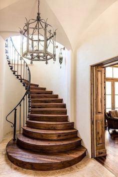 Radius steps accent the staircase, with the Iron chandelier and railing.