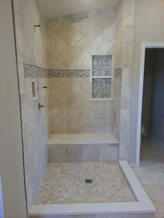 """Travertine bathroom. 6"""" deco strip with a pencil liner above and below 1/2"""" mosaic glass strip. Also soap boxes custom made inset into the wall with a picture frame around them."""