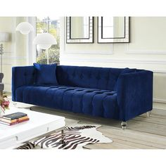 Bea Blue Velvet Sofa - TOV-S85Description :Our Bea sofa is a true a beauty. This rich velvet upholstered sofa is designed with a deep seat, luxe tufting and Lucite legs. Bea adds style and color to any room.Color : NavyMaterial : VelvetDimensions :Sofa : 90.55