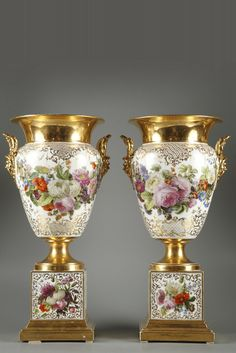 Pair of porcelain vases signed by Jacob Petit, decorated with bouquets of flowers and gilded arabesques on a white background. Each vase has two short handles adorned with masks that are topped wit...