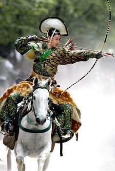 An archer dressed in traditional samurai garb displays Yabusame ~ archery while on horseback, Japan.