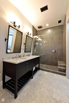 An open, walk-in shower features a glass wall, charcoal gray tile and built-in tile bench. A pair of mirrors hang above the double vanity, which provides open and hidden storage. Soft gray tiles laid in a herringbone pattern ground the space.