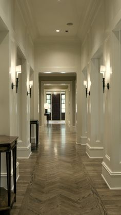 plaster work on wall, sconces & chevron laid wood in the foyer. love it all