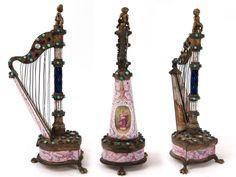 Petite harpe comprenant une montre avec mouvement Louis XV à coq Français, cadran à décor de fleurs. Mouvement signé Charles Le Roy (1765 - 1839) à Paris et numéroté 2616. Boîtier viennois émaillé forme de harpe à incrustations de nacre, turquoises et grenets, et décoré d'un scène renaissance d'anges, scène gallante de musiciens, de sabliers, dessous de la harpe à décor d'une scène érotique. Monture en bronze doré, l'ensemble est surmonté d'un chérubun. Époque 1800. Hauteur 19cm