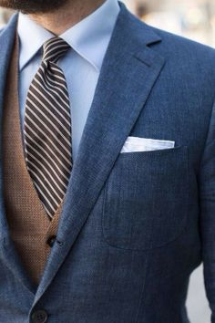 Shop this look for $154:  http://lookastic.com/men/looks/tie-and-blazer-and-dress-shirt-and-pocket-square-and-waistcoat/1716  — Dark Brown Vertical Striped Tie  — Navy Blazer  — Light Blue Dress Shirt  — White Silk Pocket Square  — Brown Waistcoat