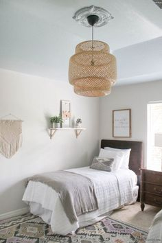 Neutral guest room with two twin beds, bamboo pendant and Harbor Haze blue ceiling