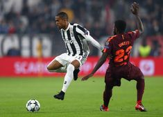 Douglas Costa of Juventus goes past Samuel Umtiti of Barcelona during the UEFA Champions League group D match between Juventus and FC Barcelona at Allianz Stadium on November 22, 2017 in Turin, Italy.