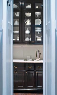 Sky blue doors and paneling lead into a tailored, black butler's pantry by Donald Lococo Architects.