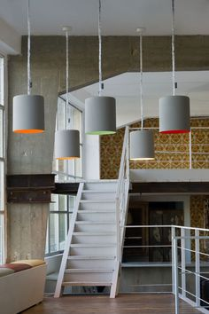 These pendant lamps are coated with concrete-effect paint with a brightly coloured interior.