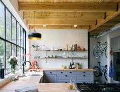 The cedar siding used on the exterior reappears throughout the house. Keen on recycling the wood, the couple added shelving to their kitchen as well.