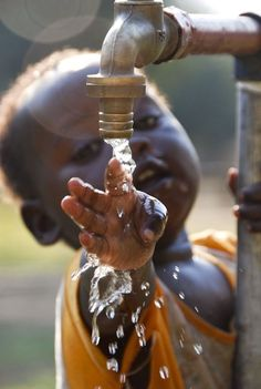 Moment: meaningful photo of a small African child touching water as it falls.