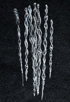 Icicle ornaments from plastic bottles. Cut 1 cm strips tapering to one end. Hold over a candle to heat. Twist and pull to get desired shape. Poke a hole with a heated needle or nail.