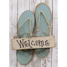 This Flip Flops sign is a wooden welcome sign shaped like a pair of blue flip flops. Made of painted, distressed wood and features jute roping and vine details.It displays the word, Welcome on of a board attached to pair of wooden flip flop sandals. Wooden Welcome Signs, Wooden Signs, Beach Crafts, Summer Crafts, Flip Flop Craft, Deco Marine, Blue Flip Flops, Beach Flip Flops, Summer Signs