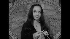 Morticia (Carolyn Jones) knitting