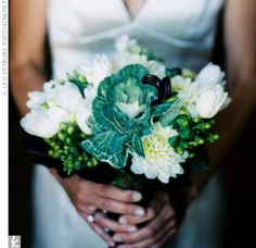 green and white blooms like kale, tulips, dahlias, ranunculus, hypericum berries, and brown fern curl wrapped in brown grosgrain