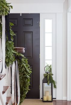 Black Door Natural Christmas Decor : Classic Christmas entry with fresh bay leaf garland and decorated lanterns Christmas Lanterns, Noel Christmas, Merry Little Christmas, Christmas Decorations, Christmas Staircase Garland, Decorating Lanterns For Christmas, Kirklands Christmas, Green Christmas, Christmas Presents