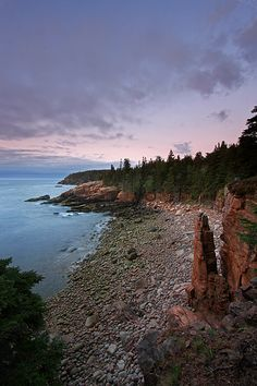 Never has land met sea in a more dramatic fashion than at Acadia National Park, Maine. This seascape photography image shows Monument Cove that is assessable from Ocean Drive and the ocean path in Acadia National Park. The beautiful cove and spot is named for its vertical sea stack of granite rock isolated from the cliff by coastal erosion. It is one of the most iconic scenes in Acadia National Park. Otter Cliff, another popular spot in Acadia, can be seen in the distance…