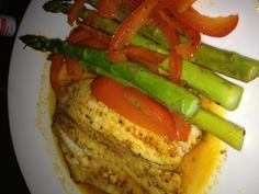 "My first Bob Harper recipe from his book ""The Skinny Rules"" Cajun tilapia with asparagus and bell peppers-minus the tomatoes. Baby steps ;)"