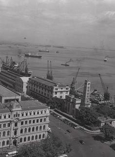Vista aérea. O Cais do Porto, no início da Avenida Rodrigues Alves: à esquerda, o Palacete D. João VI, hoje parte do Museu de Arte do Rio (MAR), erguido entre 1913 e 1918 para sediar a Inspetoria de Portos Rios e Canais. À direita, o Terminal Marítimo de passageiros do Píer Mauá